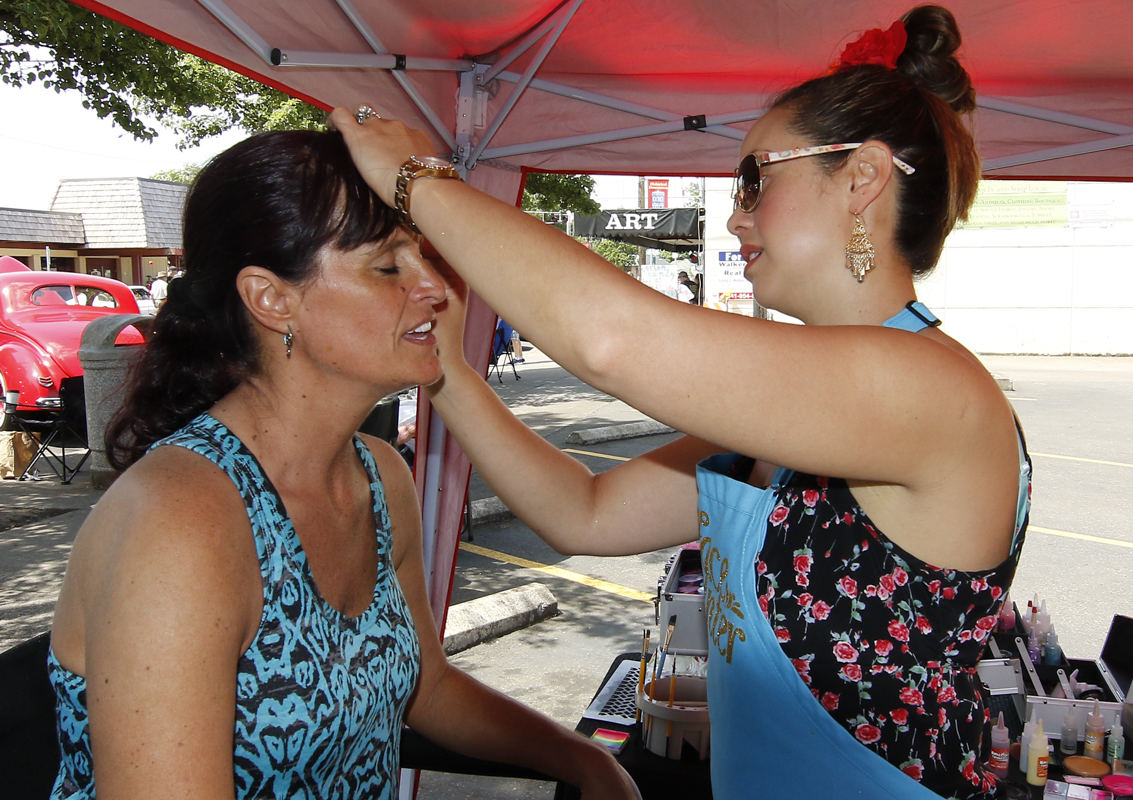 Karen Smith (L) of Philomath, Oregon, show you are never too old to get your face painted by Junction City High School graduate Chantal Wright (R) at the Show & Shine in Junction City, Oregon, June 4, 2016.